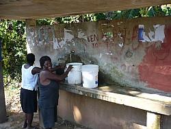 Haitian women transporting water in open buckets.