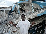 Fr. Jean Chenier-Dumais in front<br>of the ruins of his school.