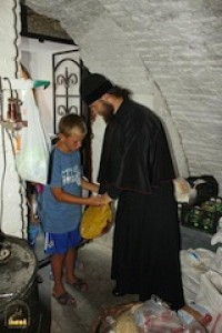 A monk gives a young refugee some provisions.